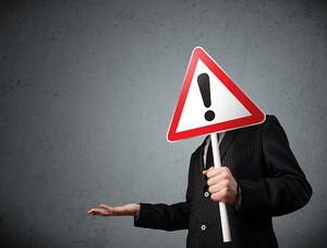 Businessman holding a red traffic triangle warning sign in front of his head