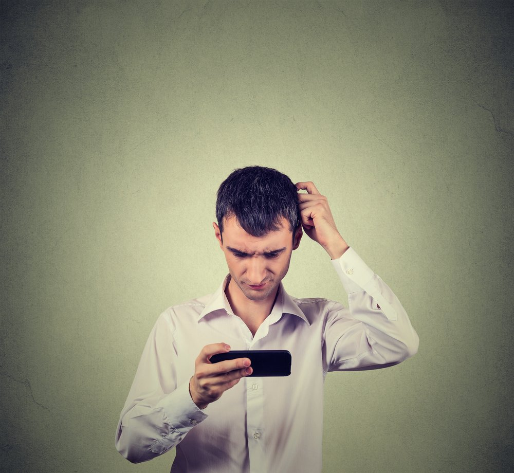 Closeup portrait perplexed young man looking at smart phone seeing bad news or photos with confused emotion on his face isolated on gray wall background. Human reaction, expression