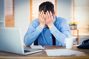 Stressed businessman with head in hands at office-1