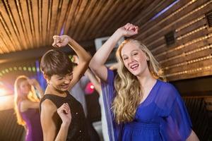 Two beautiful women dancing on dance floor in bar